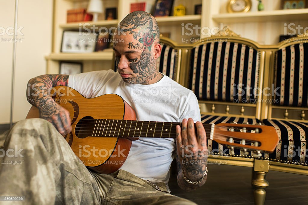 Young man sitting on the floor and playing acoustic guitar. stock photo