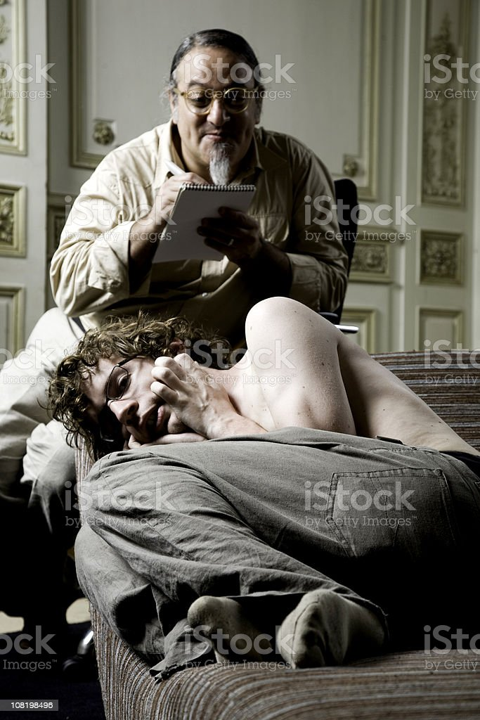 Young Man Sitting on Therapy Couch with Psychiatrist royalty-free stock photo