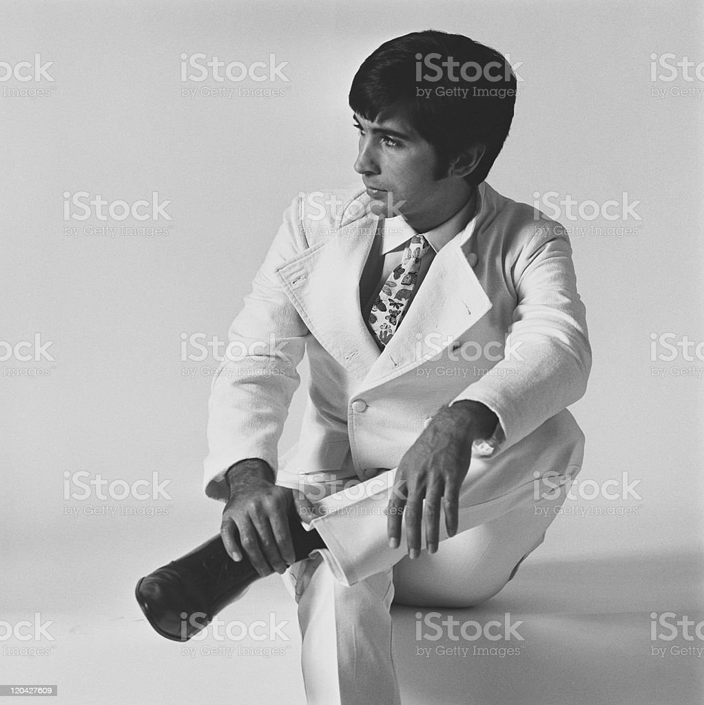 Young man sitting on white background stock photo