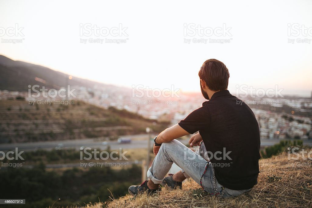 Young man sitting outdoor looking the city sun stock photo