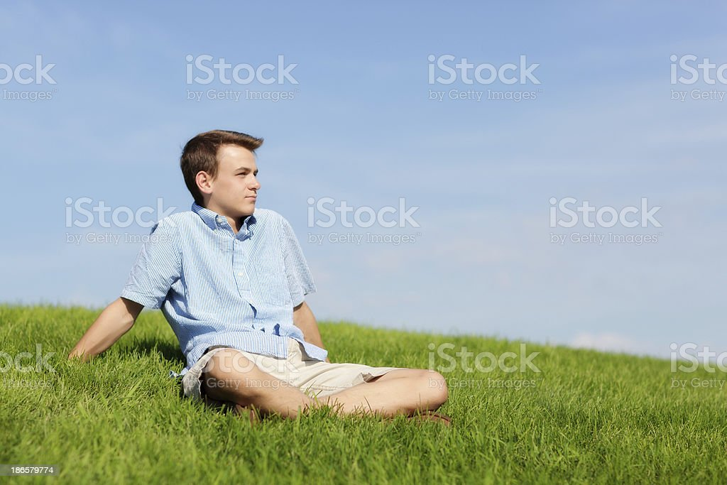 Young Man Sitting Outdoor on Grass Meadow Looking into Future royalty-free stock photo
