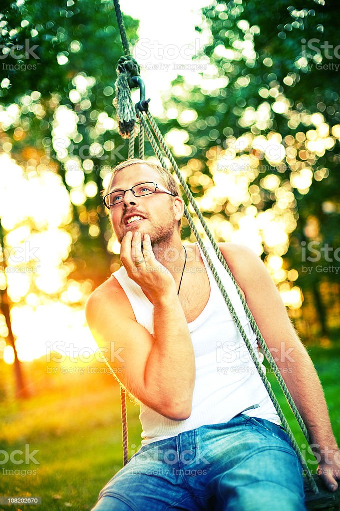 Young Man Sitting Outside on Swing royalty-free stock photo
