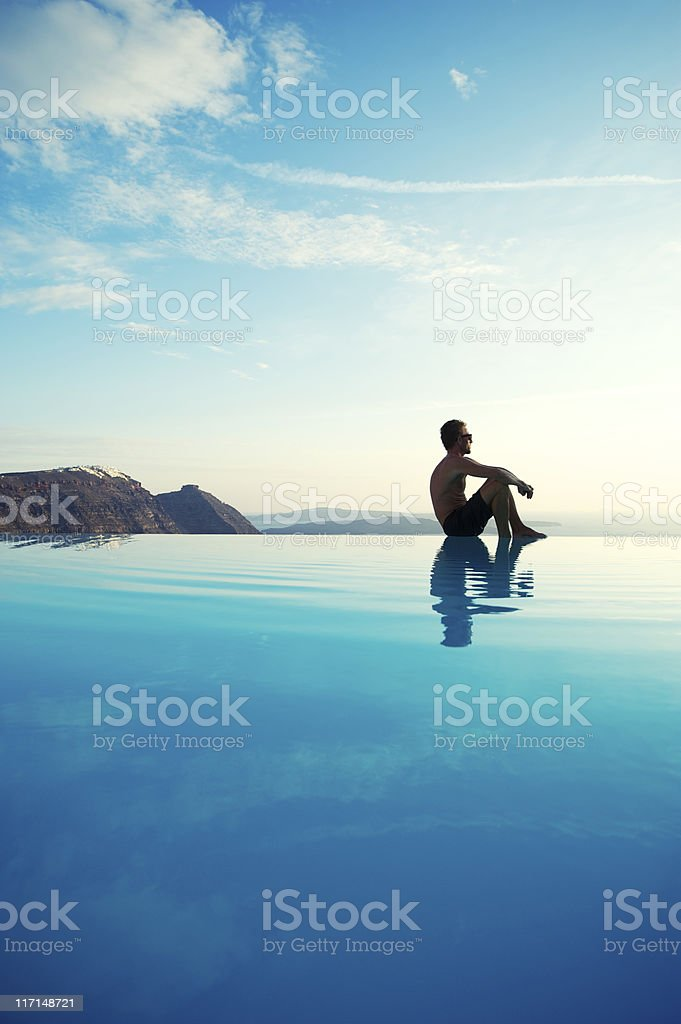 Young Man Sitting Reflecting on Infinity Pool Edge Tourist Resort stock photo