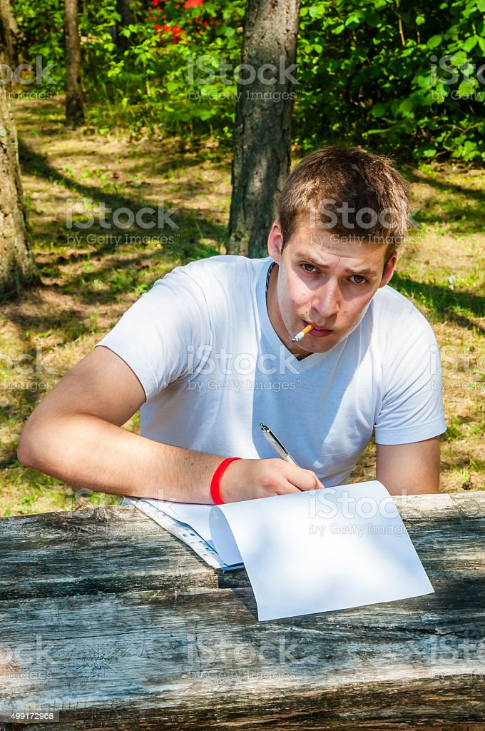 Young man sitting, smoking, editing printed text outdoors stock photo
