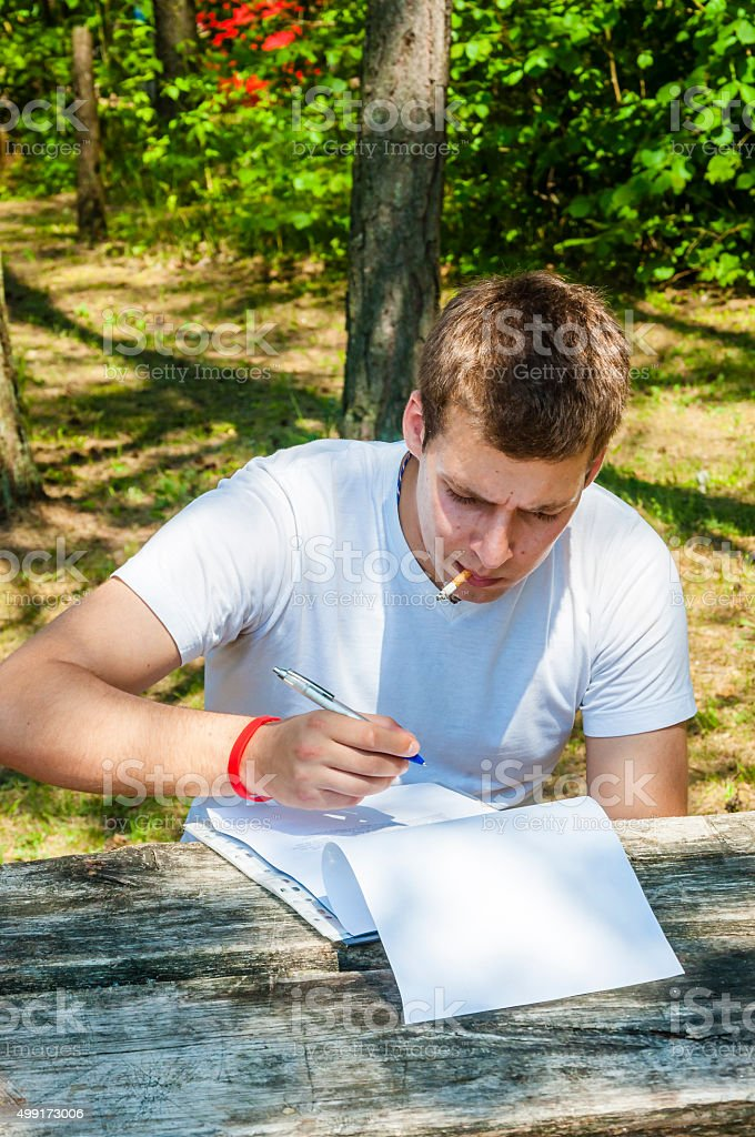 Young man sitting, smoking, thinking on printed text outdoors stock photo