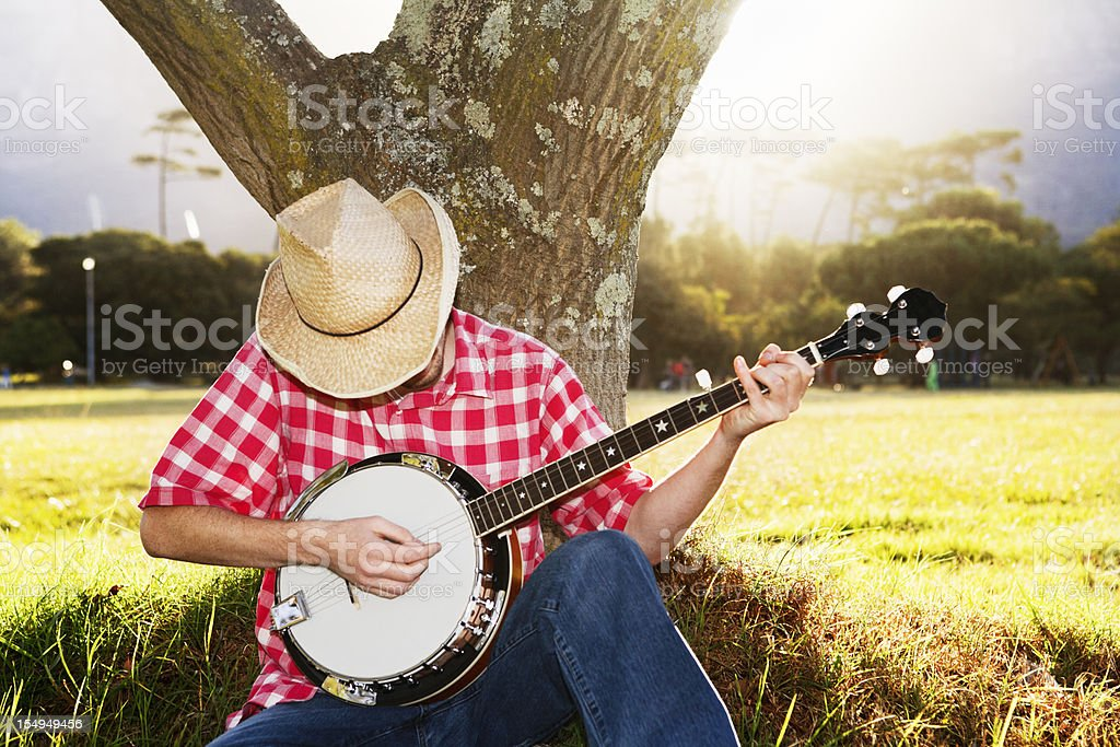 Young man sitting under tree in country playing his banjo stock photo