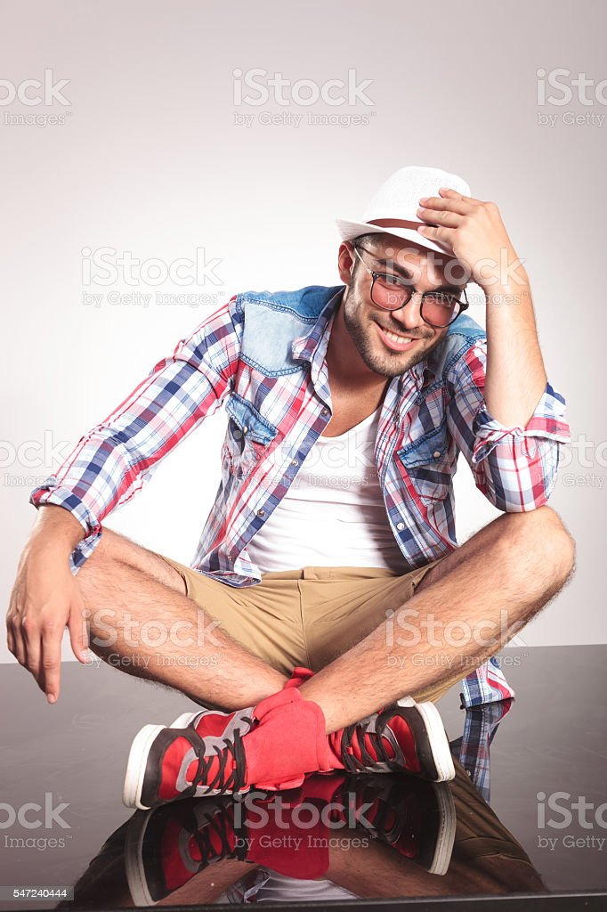 Young man sitting with his legs crossed stock photo