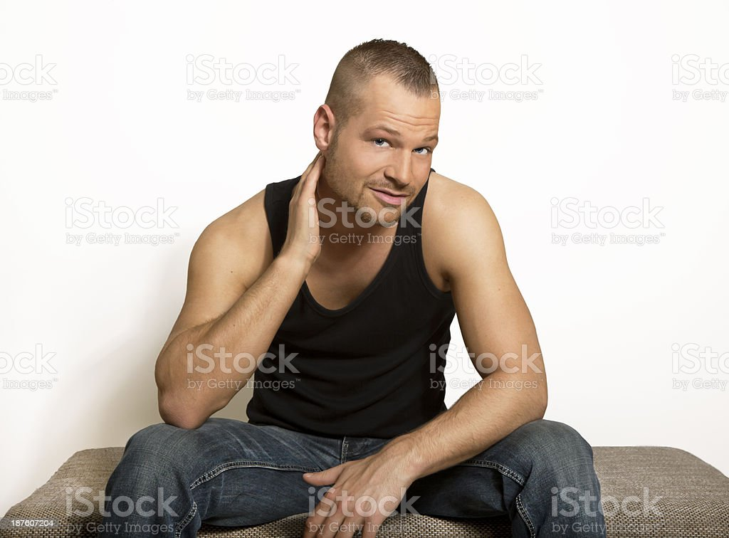 young man sitting with one hand at his head royalty-free stock photo