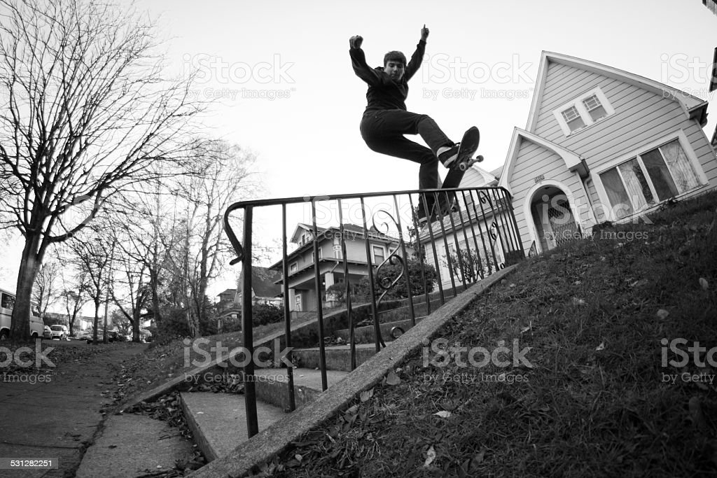 Young man skateboarding in front of residential house stock photo