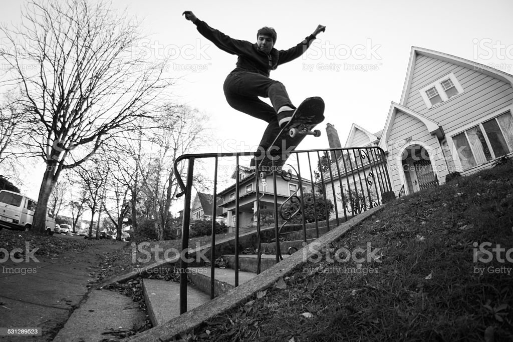 Young man skateboarding on handrail stock photo