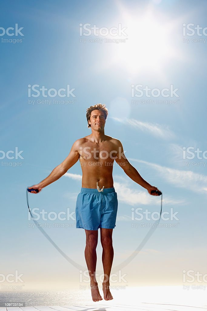 Young man skipping by the sea on a sunny day royalty-free stock photo