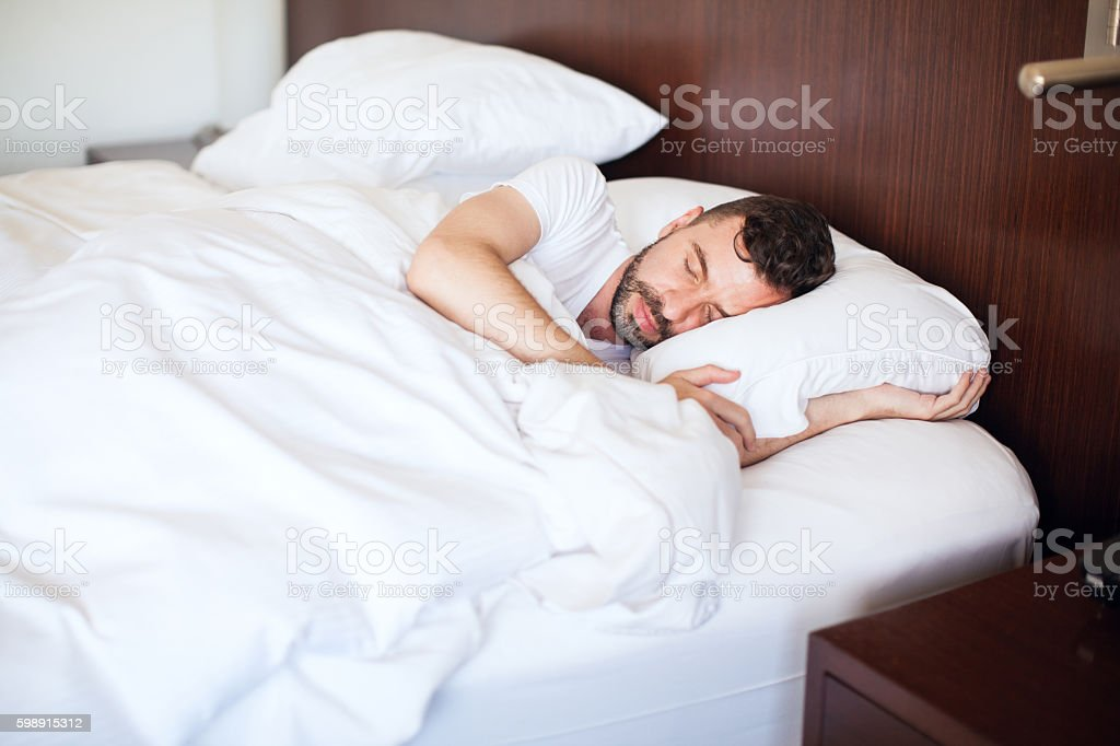 Young man sleeping in a bed stock photo
