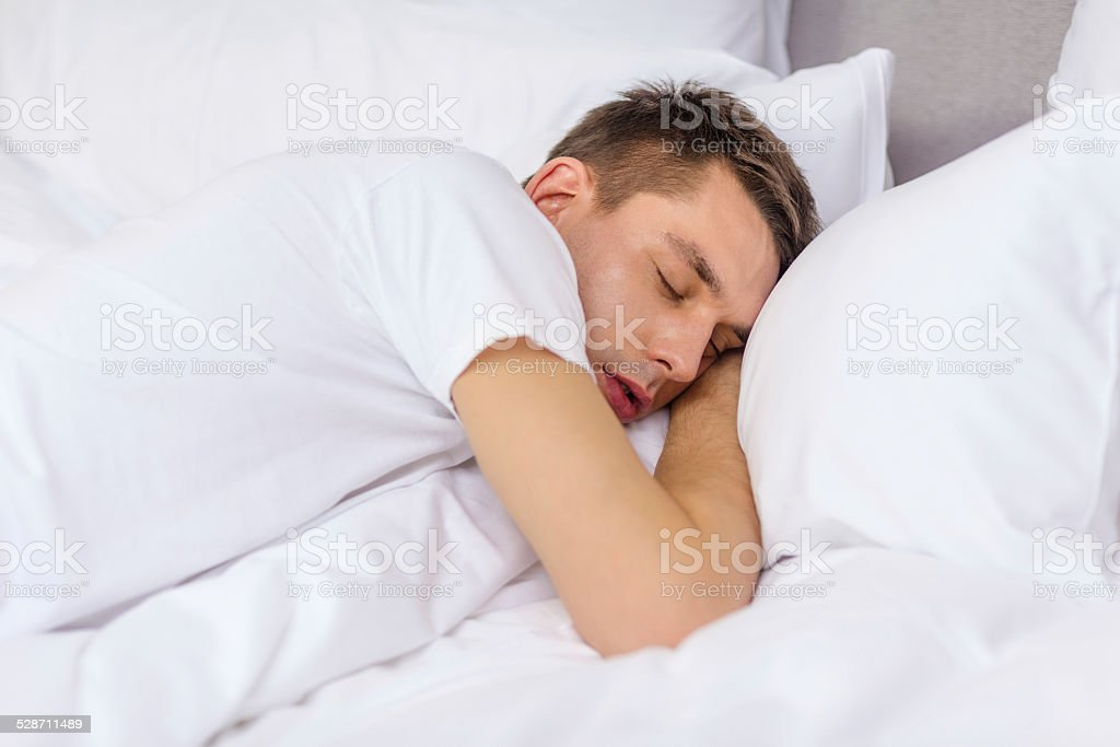 young man sleeping in bed stock photo