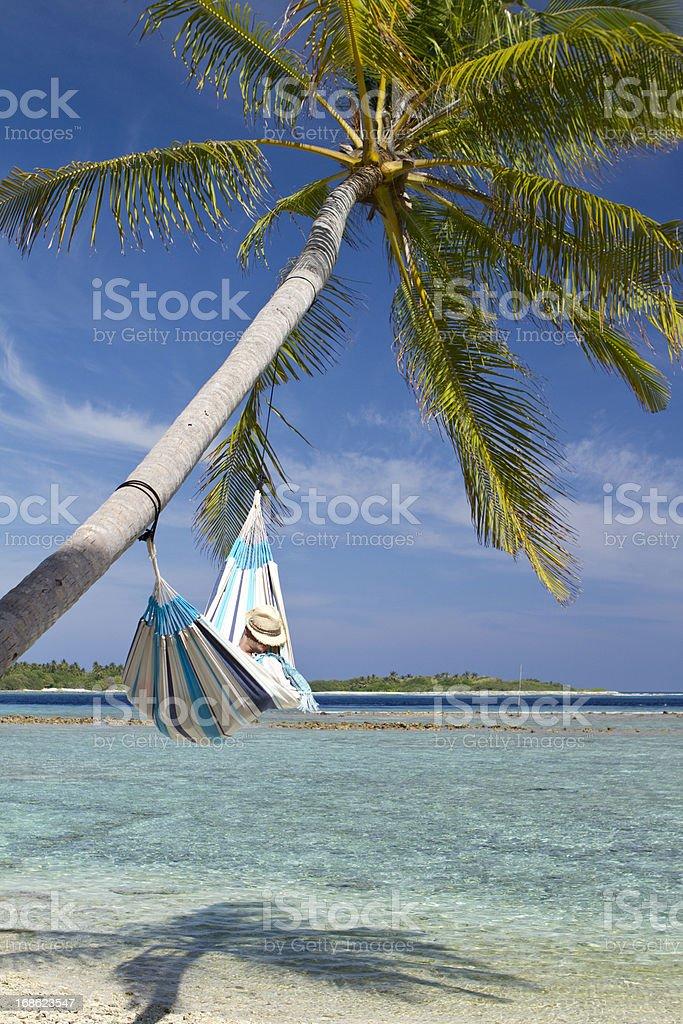 Young man sleeping in hammock on a paradisiac beach royalty-free stock photo