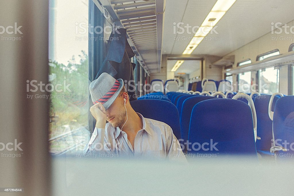 Young man sleeping in train while commuting to work stock photo