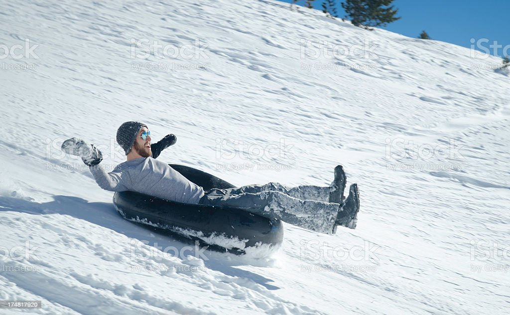 Young man sliding down a snowy hill in a black tube stock photo