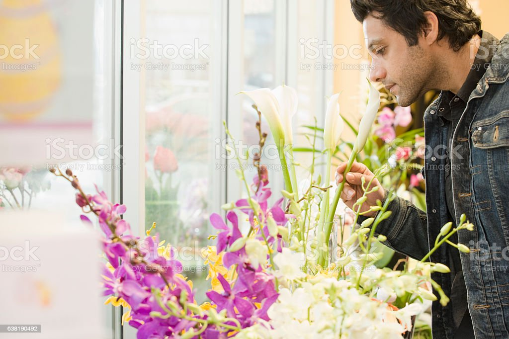 Young man smelling flower in florist shop stock photo