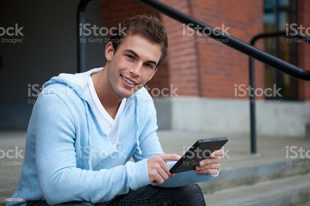 Young man smiles with tablet royalty-free stock photo