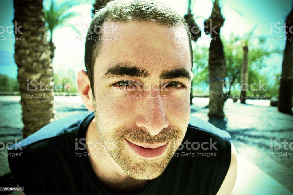 Young man smiling and looking at camera stock photo