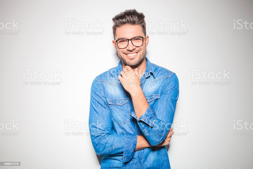 young man smiling and touching his chin stock photo