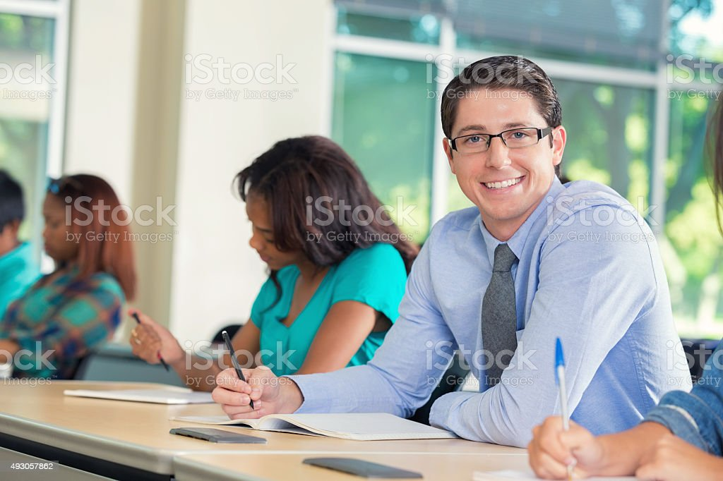 Young man smiling at camera during college class stock photo
