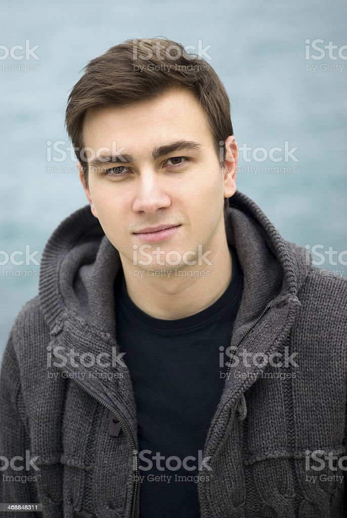 Young man smiling outdoors, portrait stock photo