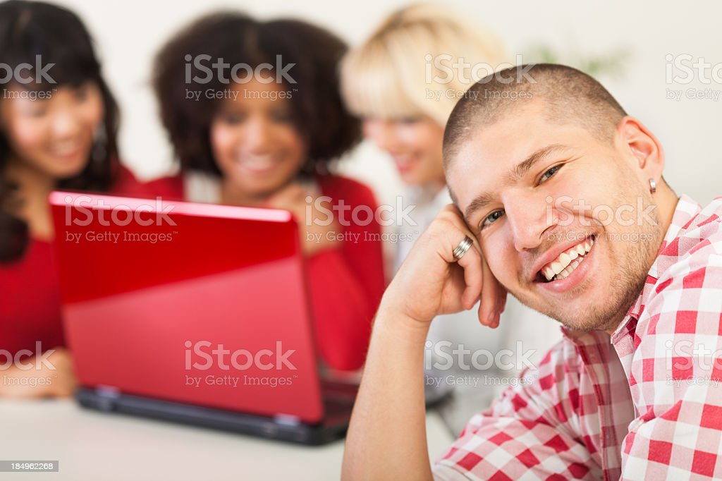 Young man smiling, people using laptop in background royalty-free stock photo