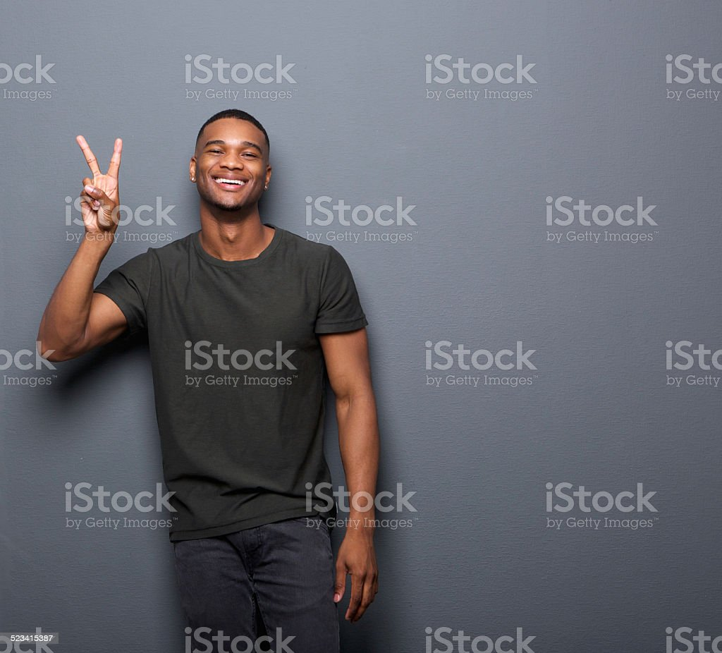 Young man smiling showing hand peace sign stock photo