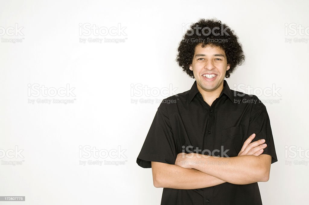 Young man smiling with his arms crossed facing the camera. royalty-free stock photo