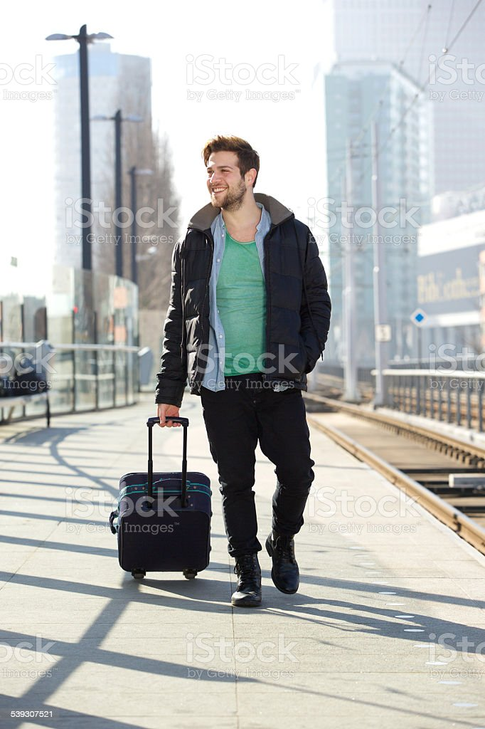 Young man smiling with suitcase on train station platform stock photo