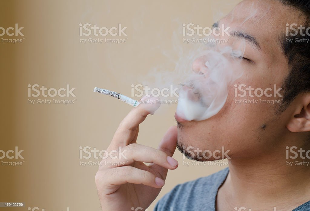 young man smoking a cigarette stock photo