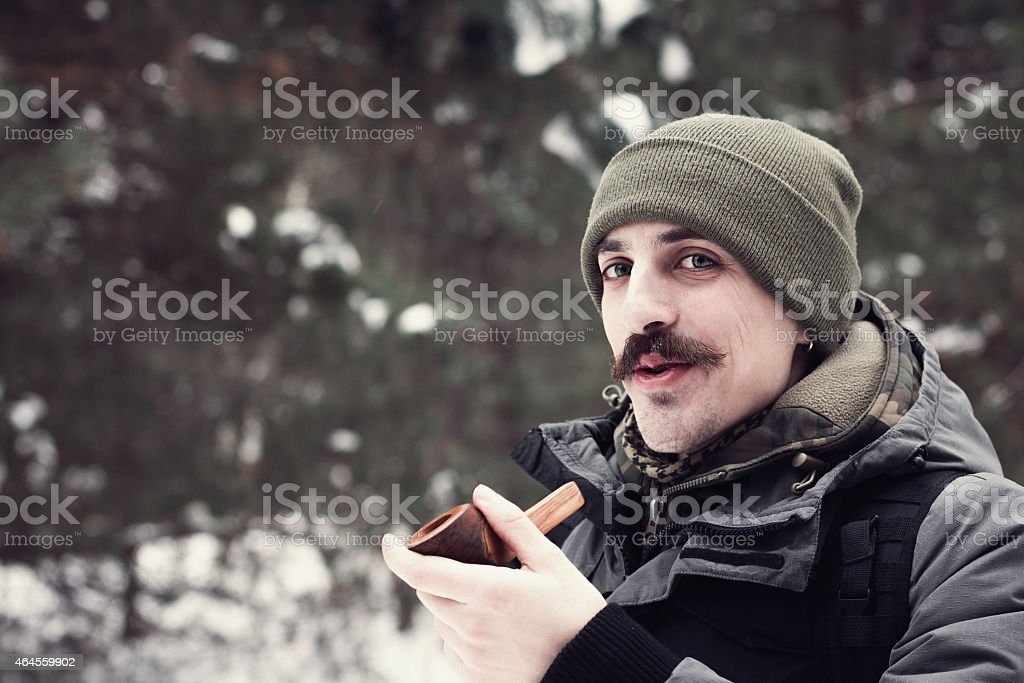 Young man smoking a pipe in forest stock photo