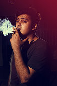 Young man smoking cigarette on dark background looking into camera