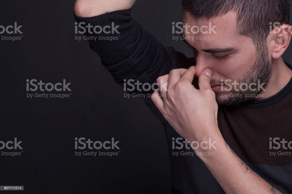Young man sniffing his underarm because of his armpit smell stock photo