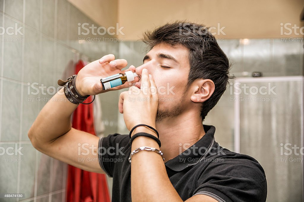 Young Man Sniffing Nose Spray in Bathroom stock photo