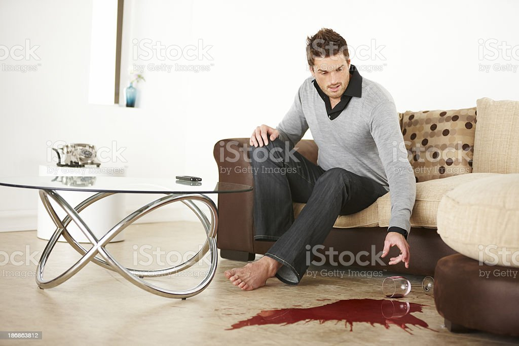 young man spilling red wine on wooden floor royalty-free stock photo