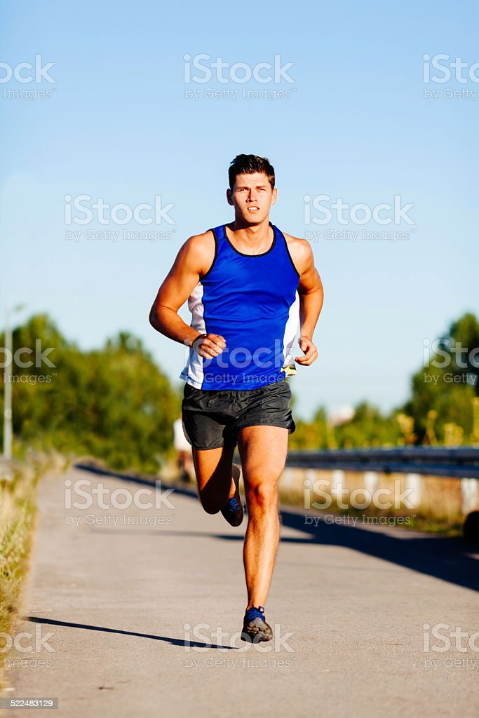 Young man sprinting stock photo