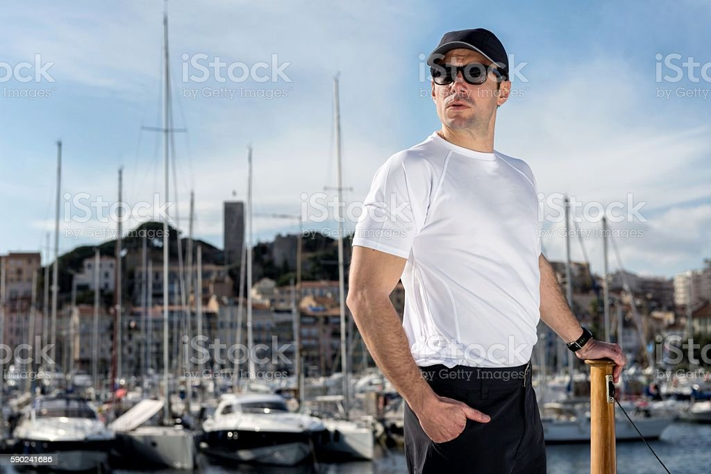 Young man standing at harbor stock photo