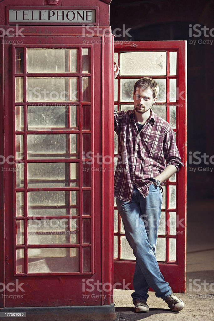 Young man standing at telephone box royalty-free stock photo