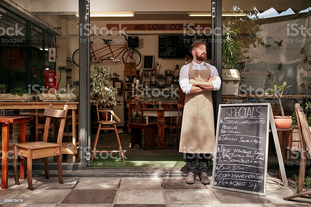 Young man standing at the entrance of his coffee shop stock photo
