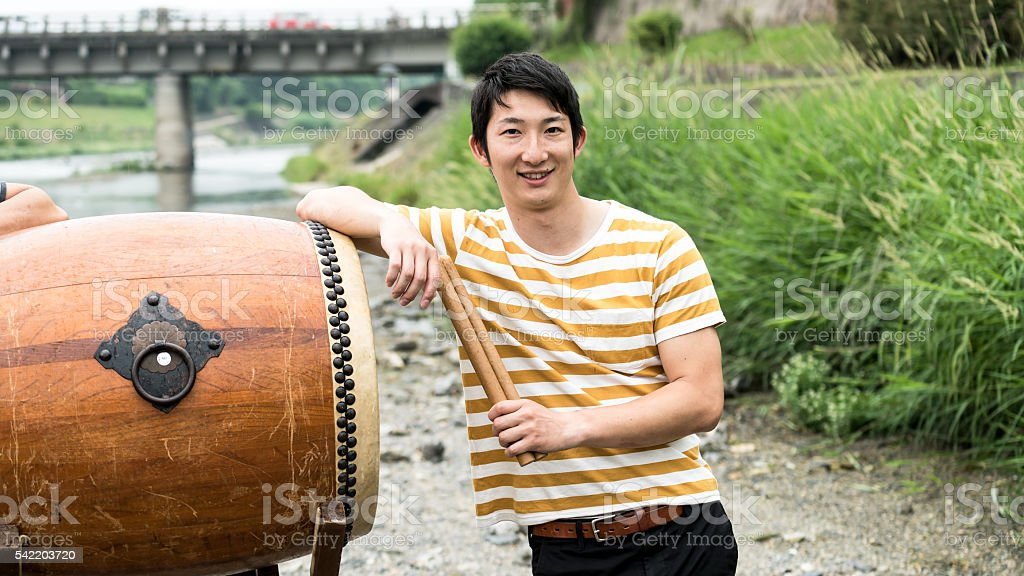 Young man standing by Japanese drum and posing stock photo