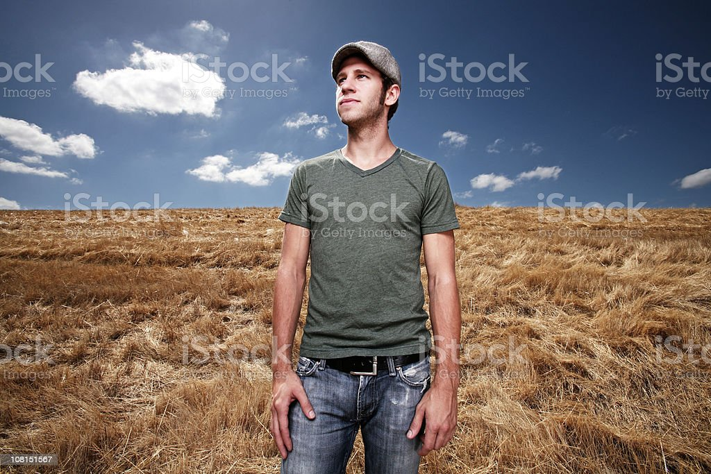 Young man standing in field royalty-free stock photo