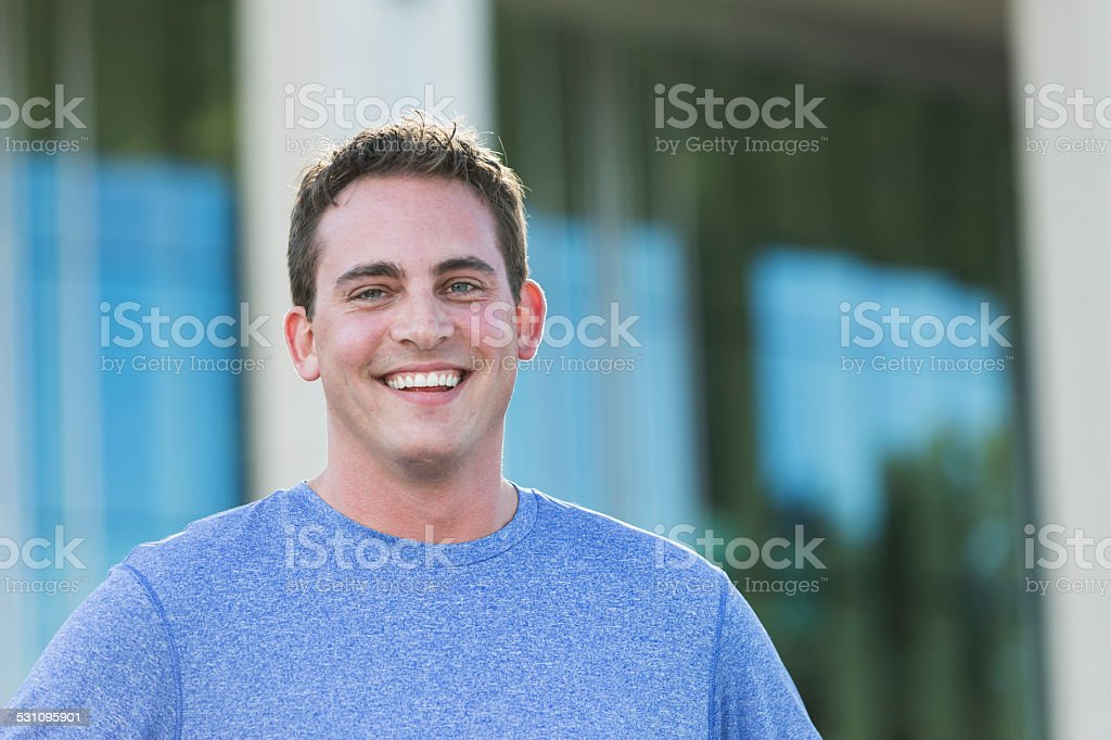 Young man standing in front of a building stock photo