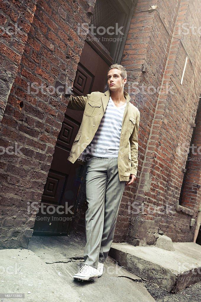 Young man standing in front of door stock photo