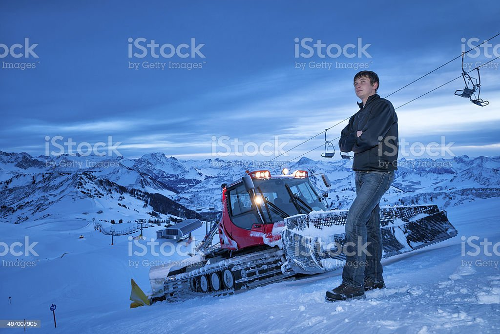 young man standing in front of snowcat stock photo