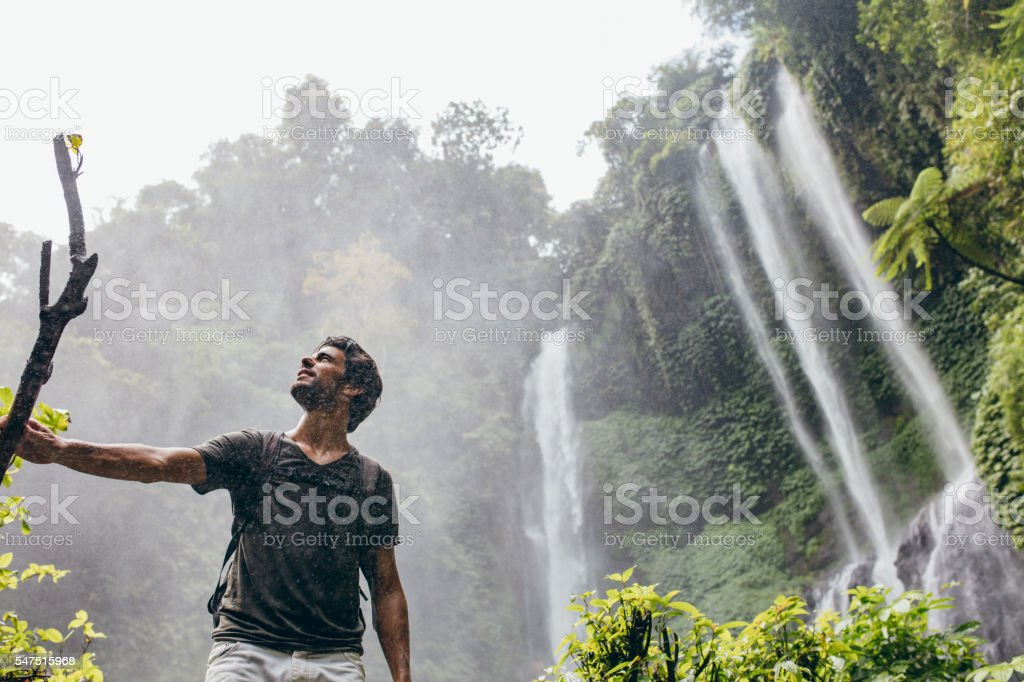 Young man standing near a waterfall in forest stock photo