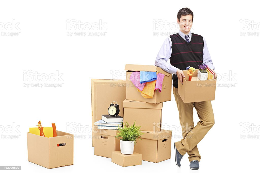 Young man standing next to a pile of boxes stock photo