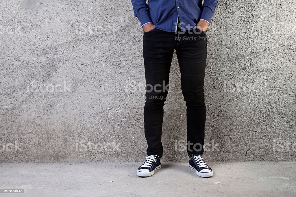 Young man standing on a concrete floor stock photo
