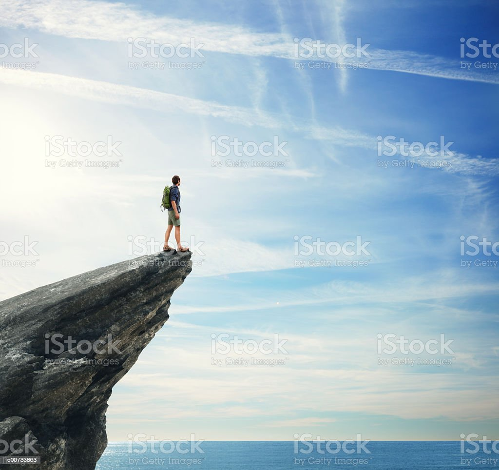 Young man standing on a peak stock photo