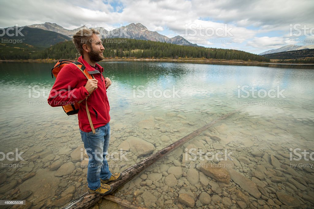 Young man standing on log above lake looking at view stock photo